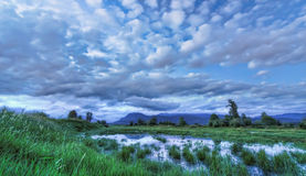 Blue Landscape with Dramatic Clouds Mountain and Water Royalty Free Stock Photos