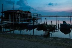Blue landscape with old boats and sheds at dusk, Italy. Blue landscape with fishing boats and sheds at dusk in venetian lagoon, Italy Stock Photography