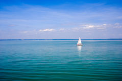 Blue landscape with sailboat Stock Photos