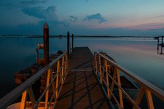 Blue landscape with wooden pier at dusk, Italy. stock images