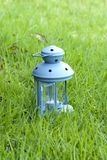 Blue Lantern, with burning candle inside, on green grass Royalty Free Stock Photos