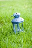 Blue Lantern, with burning candle inside, on green grass Stock Image