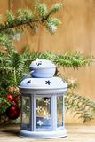 Blue lantern on wooden table, under a fir branch. Stock Images