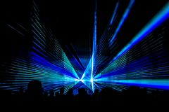 Blue laser show nightlife club stage with party people crowd. Luxury entertainment with audience silhouettes in nightclub event, festival or New Year`s Eve Stock Photos