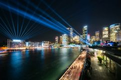 Blue Lasers cross the sky at Vivid Sydney at night. Interactive Lighting full color Laser Show at Vivid Sydney Festival 2018 in Sydney Harbour, Australia. The Stock Photos