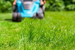 Blue lawn mower on green grass cut the grass Stock Photos