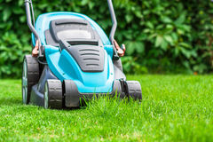 Blue lawn mower on green grass cut the grass Royalty Free Stock Photography