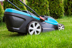 Blue lawn mower on green grass Stock Images