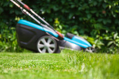 Blue lawn mower on green grass Royalty Free Stock Images