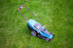 Blue lawn mower on green grass Royalty Free Stock Photo