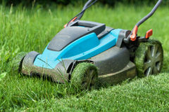Blue lawnmower cutting grass - closeup Royalty Free Stock Images
