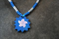 Blue Leather anBlue Leather and Pink Sunburst pendant on a Blue and Silver Chain. Horizontal Color Image of a Blue Leather and Pink Sunburst pendant on a Blue Stock Image