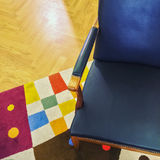 Blue leather armchair on colorful rug Royalty Free Stock Images