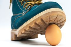 Blue leather boot stepping on the egg royalty free stock photo