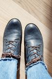 Blue leather woman`s boots. Pair of dark blue leather woman`s boots with brown shoelaces on light textured floor background stock photos