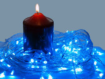 Blue LED and the candle. Two lighting technologies now in one place Stock Images