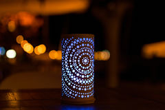 A blue led candle in the night. A blue led candle with a light pattern made by holes with some other bokeh light in the background stock photography