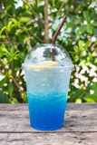 Blue lemon soda on wood table with green leaves background Royalty Free Stock Images