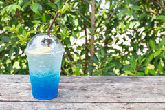 Blue lemon soda on wood table with green leaves background Royalty Free Stock Image