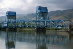 The blue Lewiston Clarkston bridge spanning the Snake River. Landscape with a blue bridge spanning the Snake River with reflections on a cloudy day Stock Photography