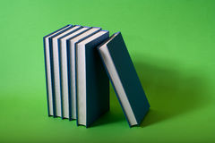 Blue library. Blue books stacked up on a green background Stock Photo