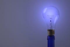 A blue light bulb on blue bottle. A blue light bulb sitting on blue bottle royalty free stock photo