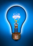 Blue light bulb with glow. Floating clear light bulb back lit by blue light Royalty Free Stock Images
