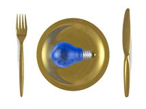 Blue light bulb with sky reflection in it, golden plate, fork and knife. Top view Royalty Free Stock Photo