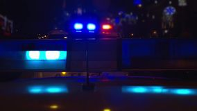 Police lights atop of a police car. Blue light flasher atop of a police car. City lights on the background stock video