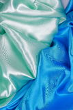 Blue and light green silk satin cloth of wavy folds texture back Royalty Free Stock Photography
