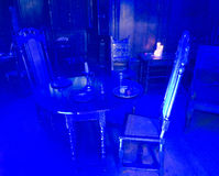 Blue light illuminating table and chairs Royalty Free Stock Images