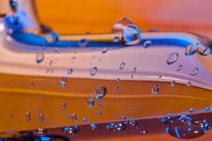 Blue lighted watter droplets on orange chromium-plated surface Royalty Free Stock Photography