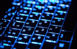 Blue lighting keyboard in the dark closeup Stock Photos