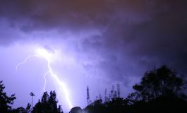 Blue Lightning over trees Royalty Free Stock Photo