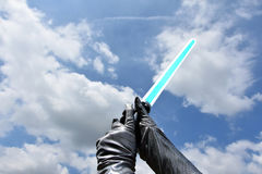 Blue lightsaber. Laser sword against the sky stock photography