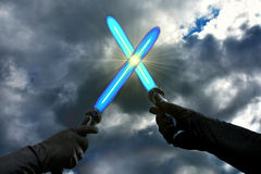 Blue lightsabers. Laser swords against the sky royalty free stock photo