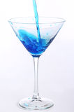 Blue liquid pouring into glass. Blue liquid pouring into martini glass Stock Photo
