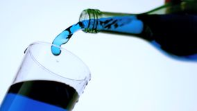 Blue liquid pouring into glass low angle close up Stock Image