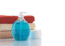 Blue Liquid Soap with Cream and Towels. Blue liquid soap with cream and different colored towels in background photographed on white (Selective Focus, Focus on Stock Photography