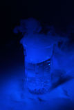 Blue lit water glass with dry ice Royalty Free Stock Photo