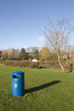 Blue  Litter. Blue litter bin on green grass with a blue sky background Royalty Free Stock Image