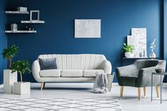 Blue living room. Interior with a white couch, grey armchair and marble decorations Stock Photo