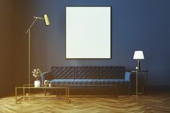 Blue living room, blue sofa, poster toned. Living room interior with a wooden floor, loft windows, a blue sofa, a coffee table and a framed vertical poster on a Stock Photos