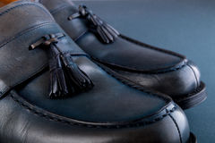 Blue loafer shoes on blue background. One pair. Close up. Royalty Free Stock Photography