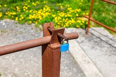 Blue lock on old rusty car ramp, with blurred yellow dandelions royalty free stock photography