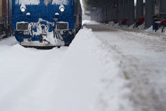 Blue locomotive train in railway station in winter time Royalty Free Stock Image
