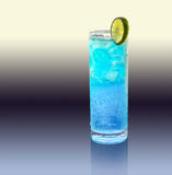 Blue longdrink with lemon. A blue longdrink with slice of lemon in gradient artificial back royalty free stock image
