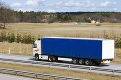 Blue lorry in countryside. Lorry, truck driving on motorway Stock Photos