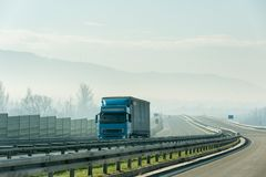 Blue lorry truck driving on asphalt highway road in a rural landscape. Blue lorry truck driving on asphalt highway road with protective fences in a rural Royalty Free Stock Images