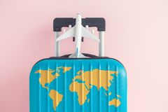 Blue luggage with world continents map and airplane toy on pastel rose background. Suitcase with world map and airplane model toy against pastel pink background royalty free stock images
